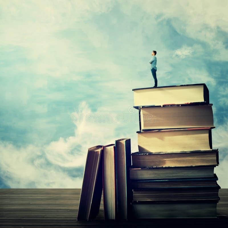 Estudante em uma pilha dos livros imagem de stock royalty free