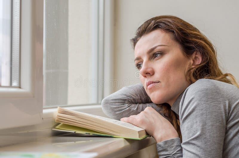 Estudante encantador nova, com o cabelo longo, triste no livro de leitura da janela com lições fotos de stock royalty free