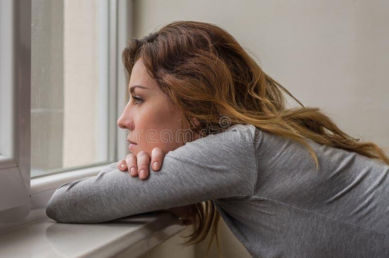 Estudante encantador nova, com o cabelo longo, triste no livro de leitura da janela com lições foto de stock