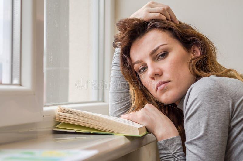 Estudante encantador nova, com o cabelo longo, triste no livro de leitura da janela com lições fotografia de stock royalty free