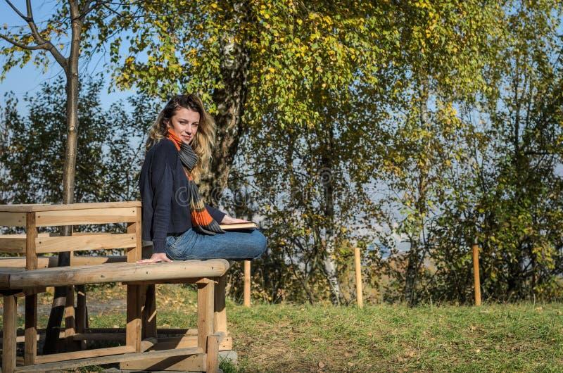A estudante encantador nova senta-se em um banco na floresta do outono e lê-se um livro foto de stock