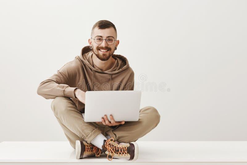 Estudante encantador que faz anotações ao estudar com amigo Homem bonito satisfeito com os vidros à moda que sentam-se sobre imagem de stock royalty free