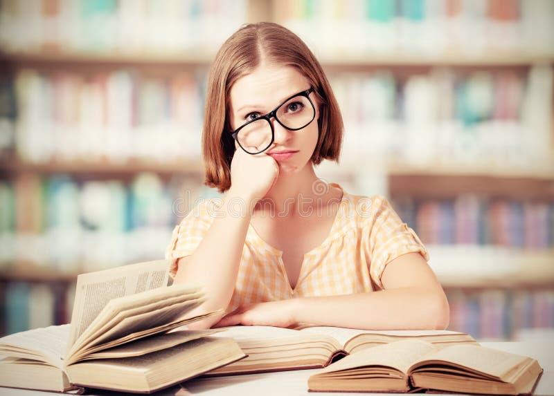 Estudante engraçada cansado com os livros de leitura dos vidros foto de stock