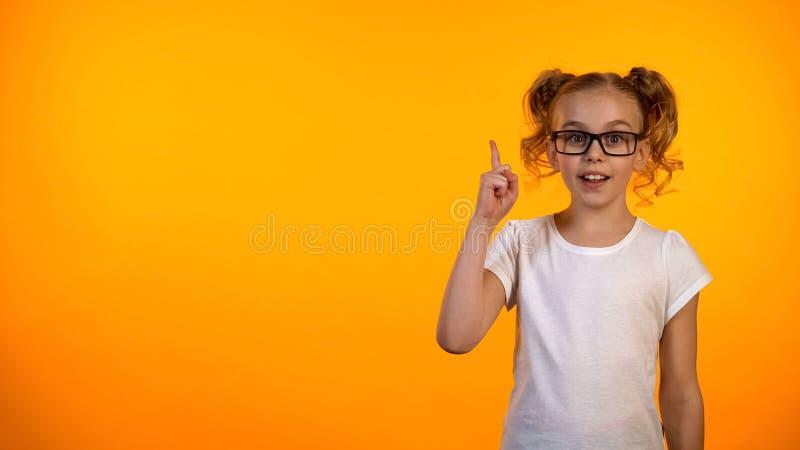 Estudante engraçada do lerdo que aumenta o dedo acima do isolado no fundo alaranjado, boa ideia fotografia de stock royalty free