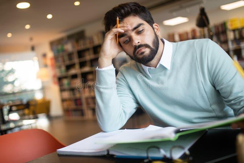 Estudante esgotado do homem novo que estuda em uma biblioteca fotografia de stock royalty free