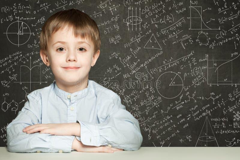 Estudante esperto bonito da criança no fundo do quadro-negro fotos de stock