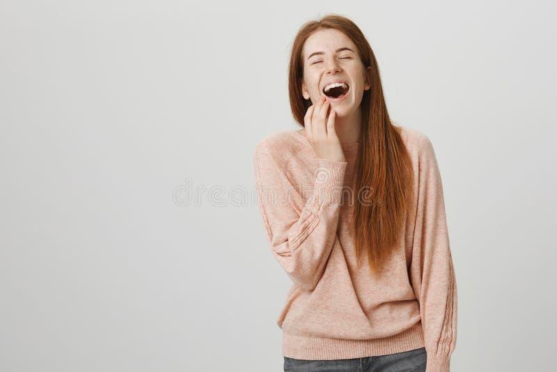 Estudante europeu do ruivo sincero encantador com sardas que ri para fora ruidosamente com olhos fechados ao tocar na cara com mã imagens de stock royalty free
