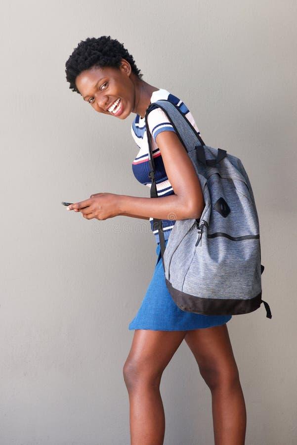 Estudante fêmea africano que anda com saco e telefone celular fotografia de stock