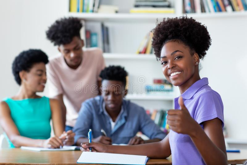 Estudante fêmea afro-americano bem sucedido que aprende na mesa na escola imagens de stock royalty free