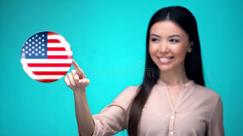 Estudante fêmea alegre que empurra o botão da bandeira dos EUA, pronto para aprender a língua estrangeira fotos de stock