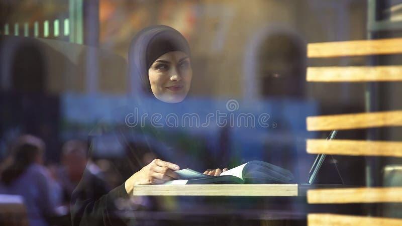 Estudante fêmea atrativo no livro de leitura árabe tradicional da roupa no café imagem de stock