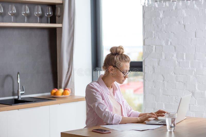 Estudante fêmea atrativo que usa seu portátil na cozinha imagens de stock royalty free