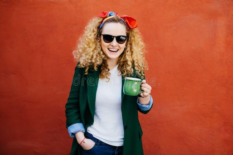 Estudante fêmea bonito com a faixa vestindo encaracolado do cabelo louro, os óculos de sol e o revestimento à moda guardando a xí imagens de stock royalty free