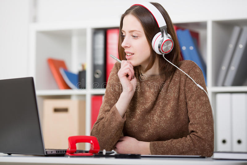 Estudante fêmea bonito com fones de ouvido que escuta a música e que aprende Guarde o punho em sua mão e a vista do monito do por fotos de stock royalty free