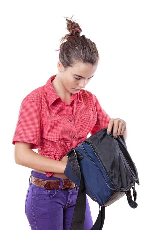 Estudante fêmea bonito que procura em um saco azul fotos de stock royalty free