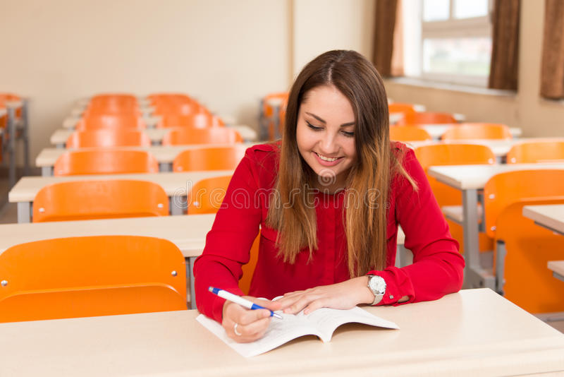 Estudante fêmea With Books Sitting na sala de aula fotografia de stock