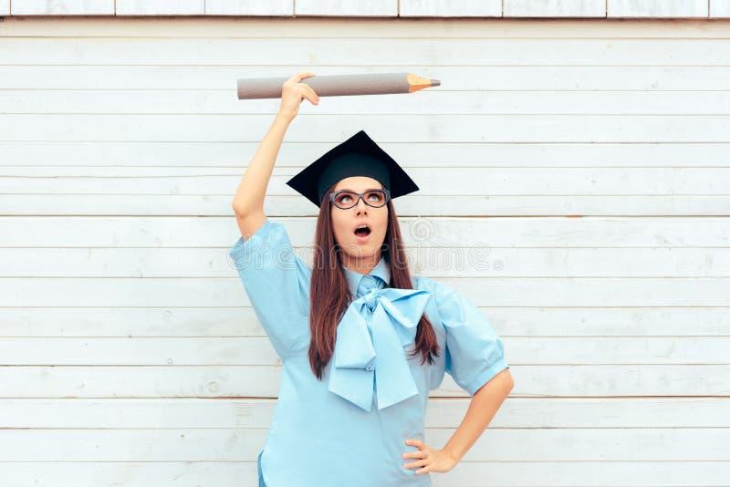 Estudante fêmea com o chapéu da graduação que guarda um lápis grande foto de stock