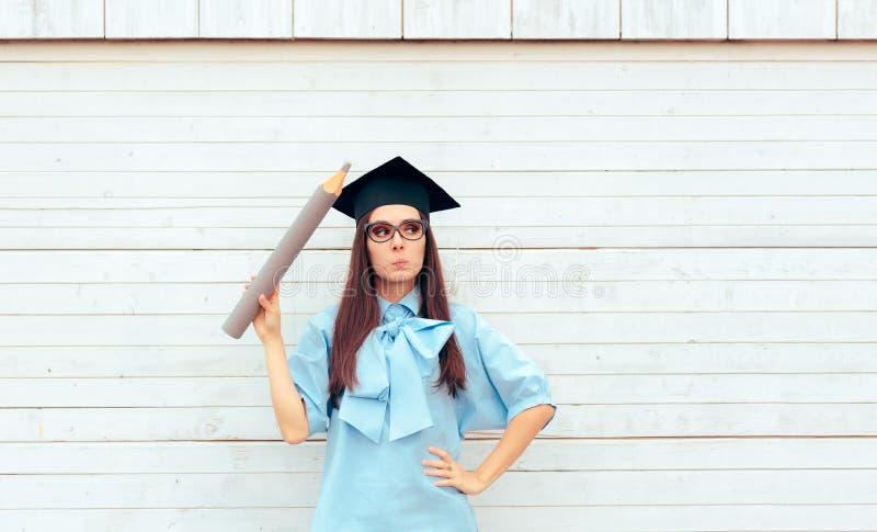 Estudante fêmea com o chapéu da graduação que guarda um lápis grande imagem de stock royalty free