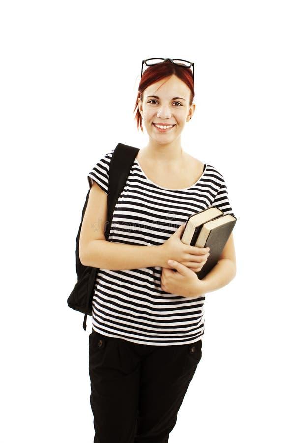 Estudante fêmea com um saco de escola que prende um livro imagem de stock royalty free