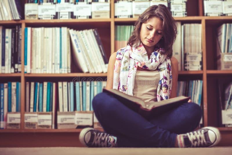 Estudante fêmea contra a estante que lê um livro no assoalho da biblioteca imagens de stock