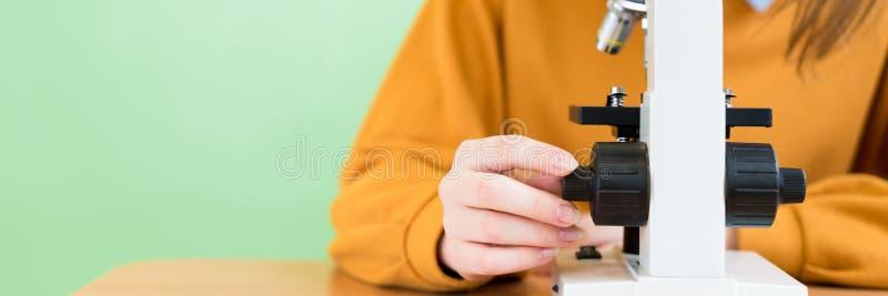 Estudante fêmea de High School na turma de Biologia Estudante que usa o microscópio fotos de stock