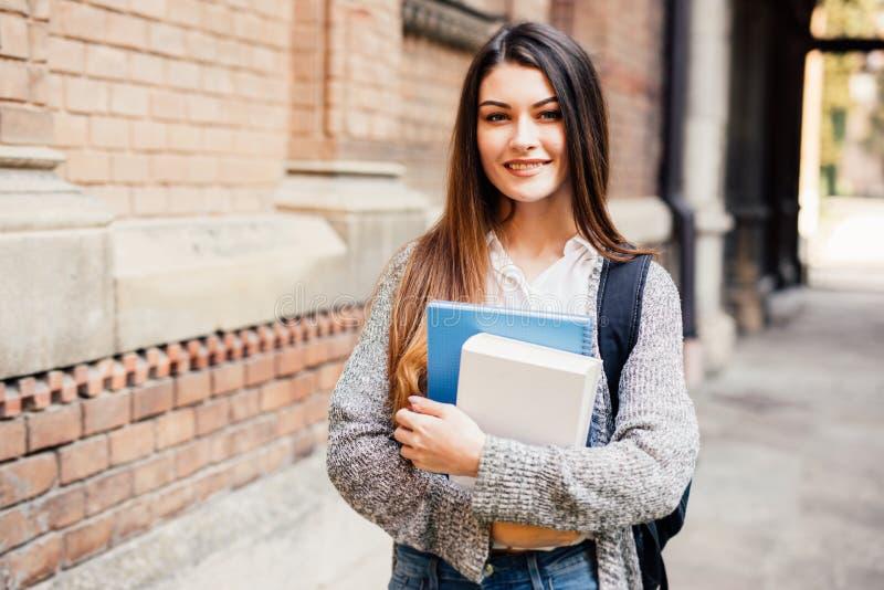 Estudante fêmea de sorriso em monóculos pretos com dobradores e saco na parte traseira foto de stock