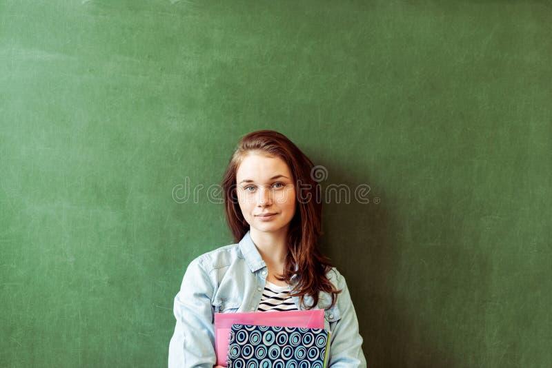 Estudante fêmea de sorriso seguro novo da High School que está na frente do quadro na sala de aula, guardando livros de texto imagens de stock