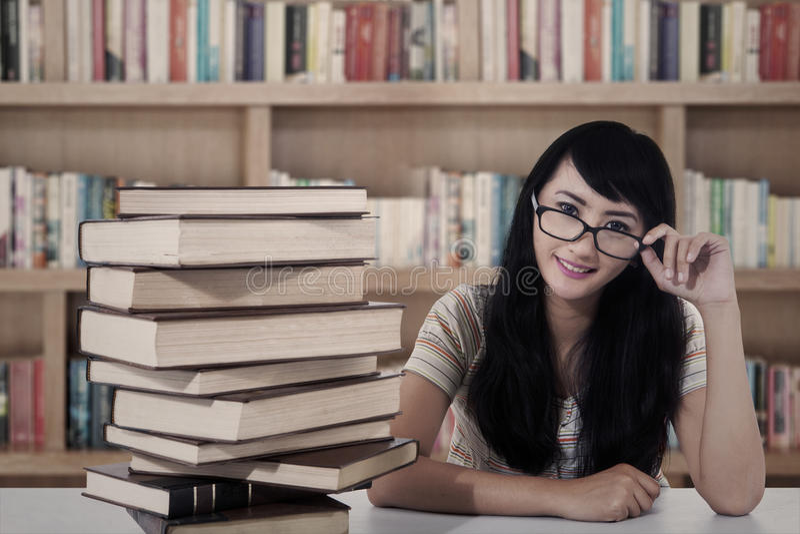 Estudante fêmea e livros atrativos na biblioteca imagens de stock royalty free