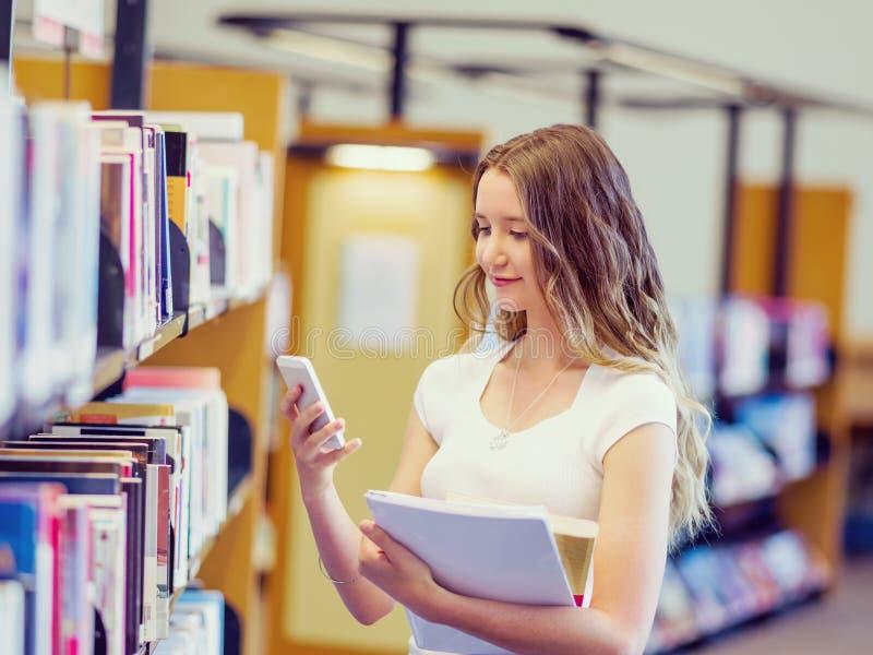 Estudante fêmea feliz que guarda livros na biblioteca imagens de stock royalty free