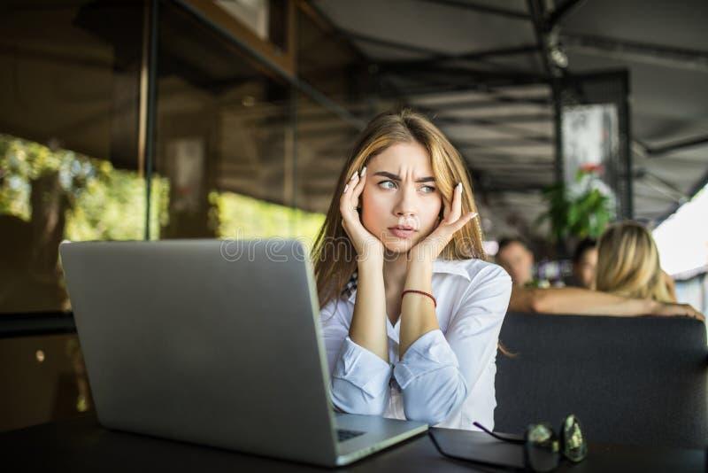 Estudante fêmea forçado que tem a dor de cabeça que toca nos templos que preparam-se para o teste no café A menina milenar frustr fotos de stock royalty free
