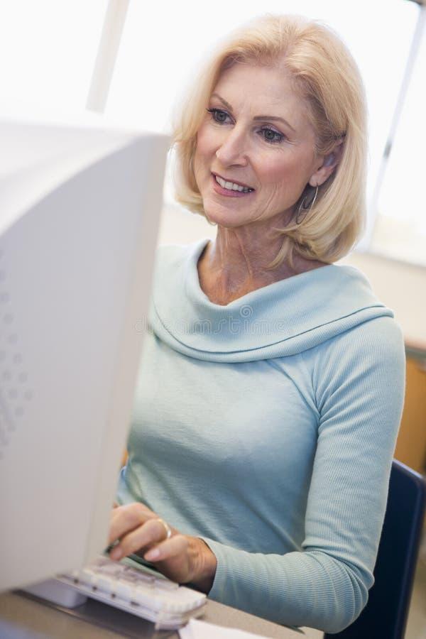 Estudante fêmea maduro que aprende habilidades do computador imagem de stock