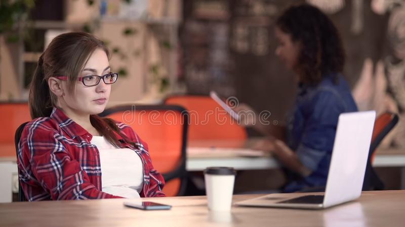 Estudante fêmea nos monóculos que olha o vídeo no portátil, descansando na barra da universidade fotos de stock royalty free