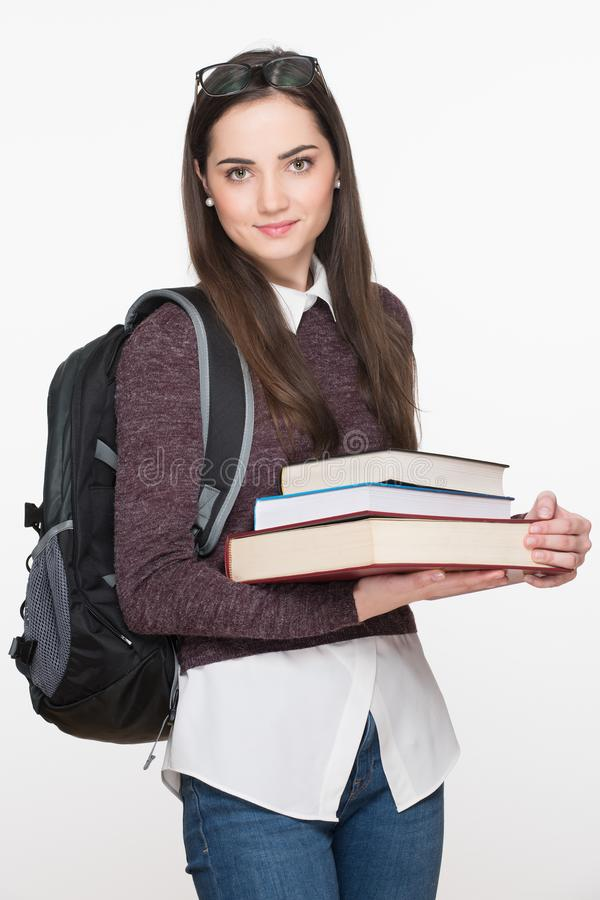 Estudante fêmea novo alegre atrativo que guarda os livros, isolados no fundo branco Conceito da instrução imagens de stock royalty free