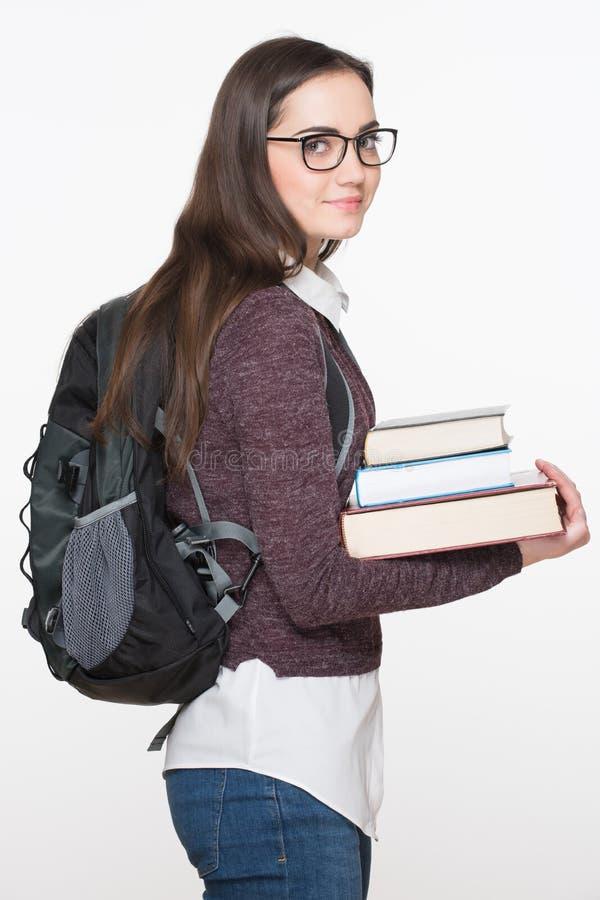 Estudante fêmea novo alegre atrativo que guarda os livros, isolados no fundo branco Conceito da instrução foto de stock royalty free