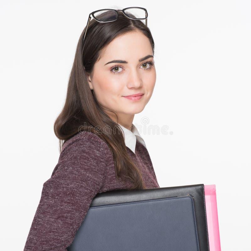 Estudante fêmea novo alegre atrativo que guarda os livros, isolados no fundo branco Conceito da instrução imagens de stock