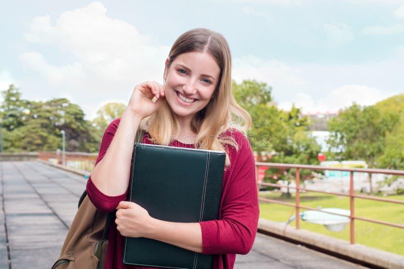 Estudante fêmea novo com os dobradores no terreno da faculdade foto de stock
