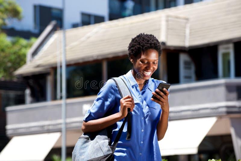 Estudante fêmea novo de sorriso que anda fora e lendo a mensagem de texto no telefone esperto foto de stock