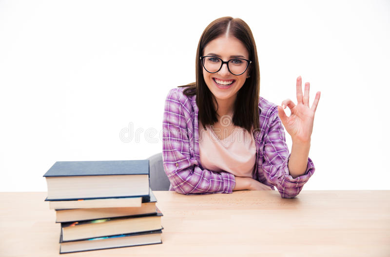 Estudante fêmea novo de sorriso que mostra o sinal aprovado fotografia de stock