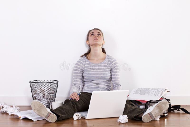 Estudante fêmea novo que senta-se no assoalho cercado por livros e por desordem imagem de stock