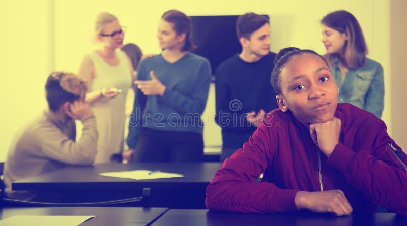 Estudante fêmea novo que sente tímido no rebaixo fotos de stock royalty free