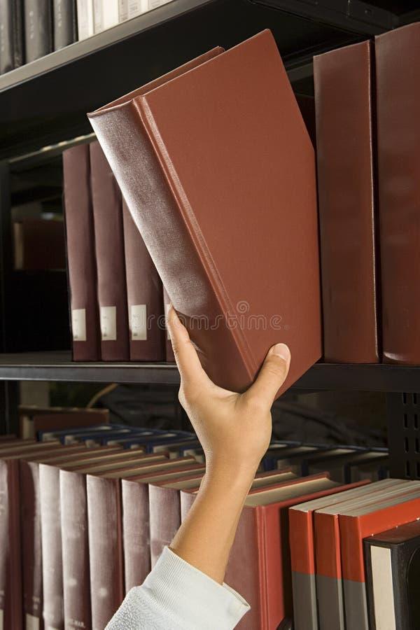 Estudante fêmea que alcança para um livro fotos de stock