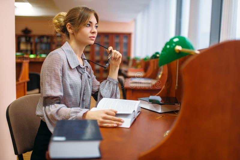 Estudante fêmea que aprende o livro na biblioteca da universidade fotos de stock royalty free