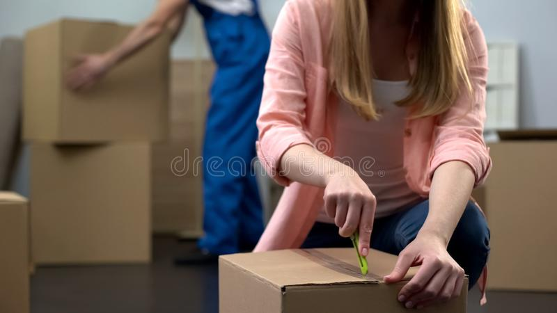 Estudante fêmea que desembala coisas na sala, bagagem levando do trabalhador da empresa de mudanças imagem de stock royalty free