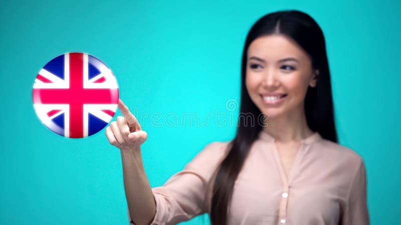 Estudante fêmea que empurra o botão da bandeira de Grâ Bretanha, pronto para aprender a língua fotografia de stock