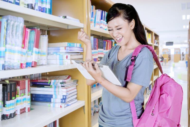 Estudante fêmea que expressa sua felicidade na biblioteca imagens de stock royalty free