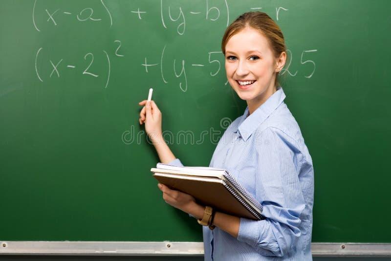 Estudante fêmea que faz a matemática no quadro imagens de stock