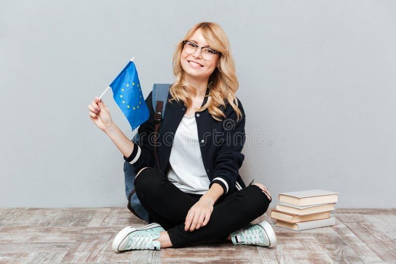 Estudante fêmea que guarda a bandeira europeia que senta-se no assoalho foto de stock