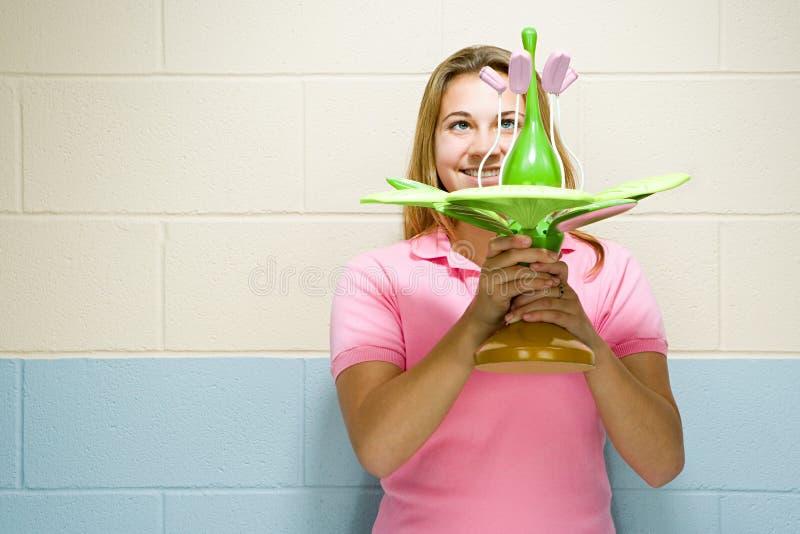 Estudante fêmea que guarda um modelo de uma planta foto de stock