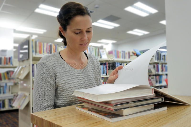 Estudante fêmea que lê um livro em uma biblioteca fotografia de stock royalty free