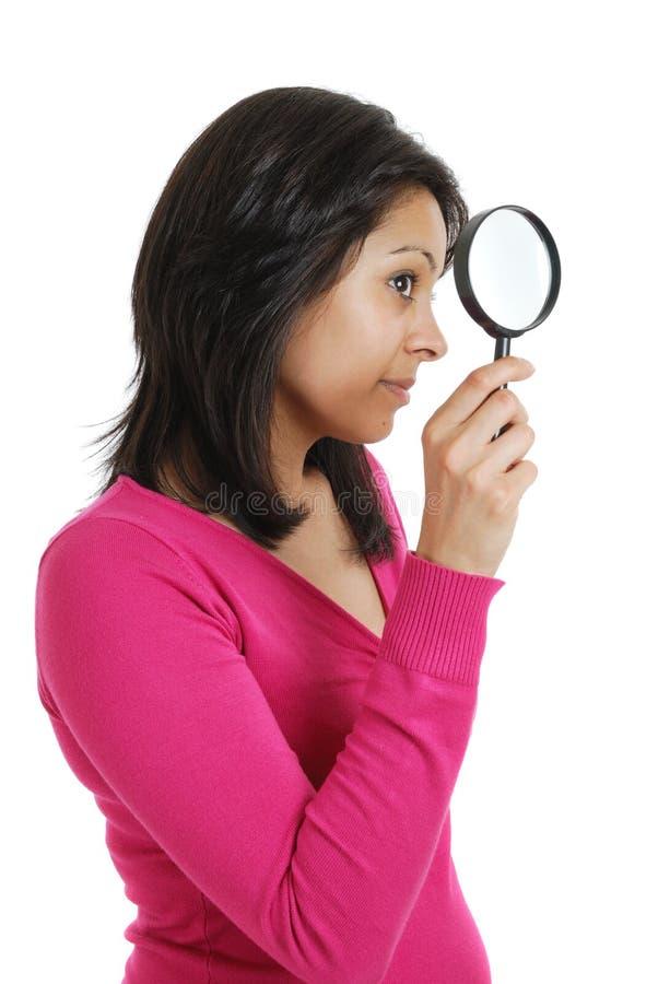 Estudante fêmea que olha através de uma lupa foto de stock